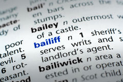 Definition of Bailiff. The word Bailiff in a dictionary, word in blue with rest of page text in black Royalty Free Stock Image