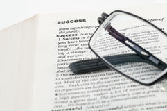 Definition of success. In a dictionary with a pair of glasses on it Stock Image