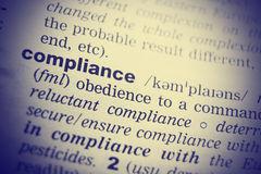 Definition of the word Compliance. Toned image.  Royalty Free Stock Photo
