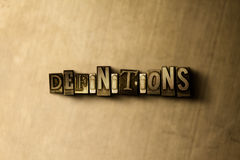 DEFINITIONS - close-up of grungy vintage typeset word on metal backdrop Stock Photography