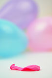 Deflated Balloon. One deflated balloon with colorful balloons in the background Royalty Free Stock Photo