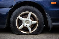 Deflated car tire on a rusted wheel. Deflated tire of an old rusted car. Car wheel with rubber tire with no air stock photos
