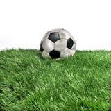 Deflated soccer ball. Deflated football ball on grass stock images