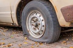 Deflaterat skadat däck på bilhjulet Arkivbilder