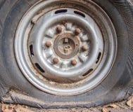 Deflaterat skadat däck på bilhjulet Arkivbild