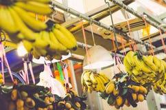 defocus射击了异乎寻常的热带水果,在市场摊位的黄色香蕉显示 库存照片