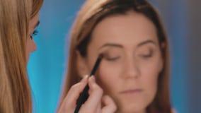 Defocus,化妆师在眼睛的眼皮上把暗影放,与在a的面孔的一把专业刷子 股票录像