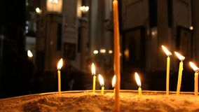 Defocus świeczki są oparzenie i pozycją w piasku w candlestick w Ortodoksalnym kościół zbiory