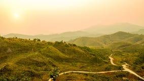 Defocus av berglandskapet och dalvägen med orange himmel på solnedgången, Thailand Bakgrund av kullelandskapet Natur och enviro Royaltyfri Fotografi