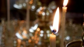 Defocus candles are burns in an Orthodox church against the wall of the high temple stock video