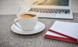 Defocus coffee cup on ground with notebook and laptop,morning,hot coffee royalty free stock image