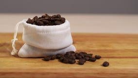 Defocus dei chicchi di caffè in un primo piano bianco del sacchetto su un tagliere 4K stock footage