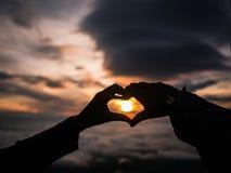 Defocus del segno della mano del cuore della siluetta con alba fotografia stock