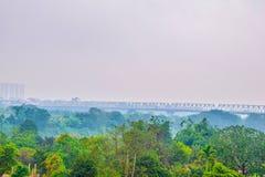 Defocus eller ut ur fokusen som vägen bygger ovanför skogen under regn och dimma i morgonen på Hanoi, Vietnam, härlig natur royaltyfri fotografi