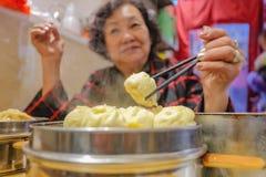 Defocus höga asiatiska kvinnor som äter små ångabullar i kinesisk restaurang royaltyfri foto