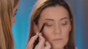 Defocus, the make-up artist puts dark shadows on the eyelids of the eyes, with a professional brush on the face of a. Caucasian blonde model. Close-up, make-up stock video footage