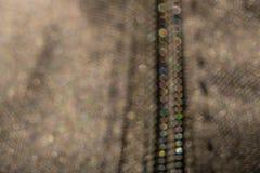 Defocus mit farbigem bokeh Reißverschluss auf einer dunklen Jacke in der Makrophotographie lizenzfreies stockbild