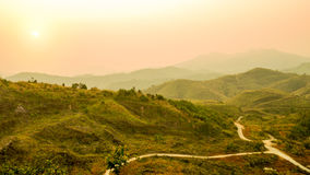 Defocus of mountain landscape and valley road with orange sky at sunset, Thailand. Background of hill landscape. Nature and enviro Royalty Free Stock Photography