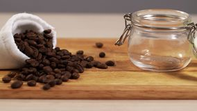 Defocus of roasted coffee beans closeup scattered on table with small jar of 4K. Defocus of roasted coffee beans closeup scattered on table with a small jar of stock video