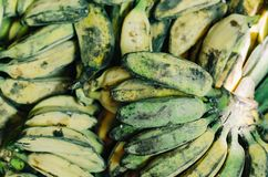Defocus shot of exotic tropical fruit, green banana display at market stall. Selective focus shot.image may contain some grain and noise Royalty Free Stock Photo