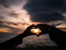 Defocus of Silhouette Heart Hand sign with Sunrise stock photography