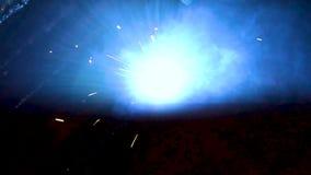 Defocus spatter from welding welder in the dark. Performs welding of metal with a welding machine stock video