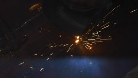 Defocus spatter from welding welder in the dark. Performs welding of metal with a welding machine stock footage