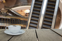 Defocus with terrace wood and cappuccino coffee with escalators. In shopping mall for background usage Stock Photos