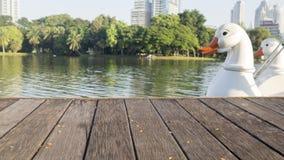 Defocus und Unschärfebild des Terrassenholzes, der weißen Enten und des Wassers, Lizenzfreie Stockfotos