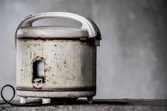 Defocus van oud wit elektrisch rijstkooktoestel werd geplaatst op de rand van de cementmuur, Oud elektrisch roestig rijstkooktoes royalty-vrije stock afbeeldingen
