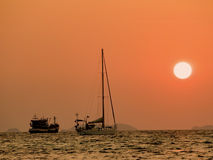 Defocus of Yachts in the sea at sunset. Silhouette boat at sunset over the sea with orange sky in background Stock Photo