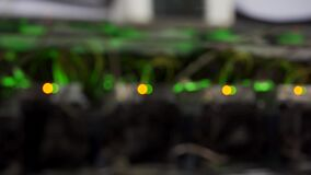 Defocus zoom. Wired internet datacenter storage. Cryptocurrency mining equipment on large farm. ASIC miners on stand