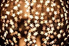 Defocused żółtego złota gwiazdy błyskają zdjęcia royalty free