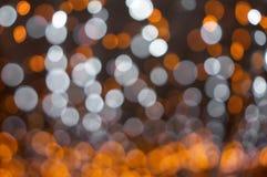 Defocused апельсин и белые светы Стоковые Фотографии RF