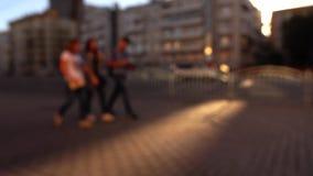 Defocused городская улица в вечере Автомобили и идя люди съемка bokeh предпосылки 4K широкая акции видеоматериалы