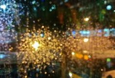 Defocused золотая светлая сцена искры шины города в ненастной ноче Стоковое Изображение RF