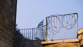 Defocused израильский флаг развевая за загородкой колючей проволоки видеоматериал