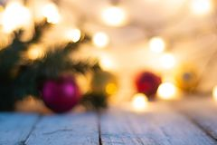 Defocused предпосылка рождества с ветвью, светами и безделушками дерева на белом деревянном столе с космосом экземпляра стоковое изображение rf