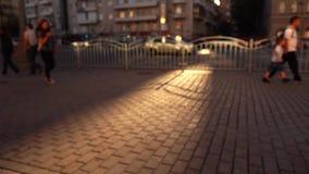 Defocused улица в вечере Автомобили и идя люди съемка bokeh предпосылки 4K широкая видеоматериал