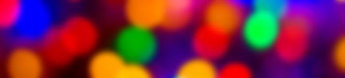 Defocused abstract multicolored bokeh lights wide banner background. Blue, purple, green, orange colors. - christmas and new year stock image