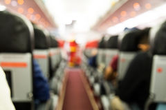 Defocused airplane cabin interior with seats and passengers Stock Photo