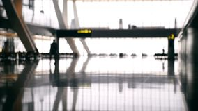 Defocused airport baackground. Silhouette people walking at the airport stock footage