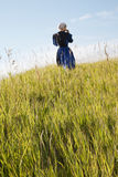 Defocused Amish woman walking in a field. A defocused Amish woman in blue and black walking in a field of grass Royalty Free Stock Photo