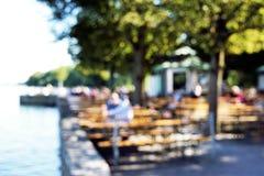 Defocused beergarden background. Defocused bokeh background. people sitting in beergarden at lake Royalty Free Stock Images