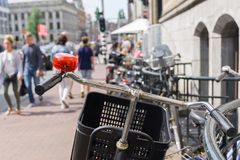 Defocused blur street scene. Focus on bicycle hanle bars and red bell in defocused blur background street scene with railing, and unrecognizable people Royalty Free Stock Photo