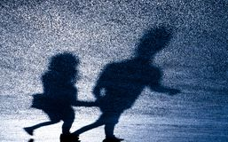 Defocused blurry shadow silhouette of young couple. Holding hands while walking on asphalt road in the night stock photo