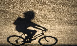 Defocused blurry shadow silhouette of a young person riding a bi. Ke on sunset shiny asphalt road Stock Photos