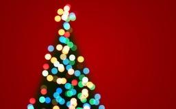 Defocused bokeh des Weihnachtstannenbaums beleuchtet Hintergrund Lizenzfreie Stockfotos