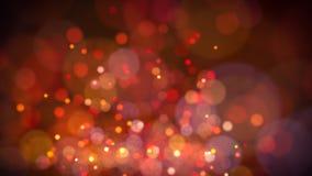 Defocused bokeh Hintergrund von roten und goldenen funkelnden Scheinen und von Lichtern Stockfotos