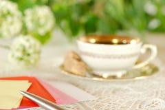 Defocused breakfast table in the garden with writing belongings Stock Image